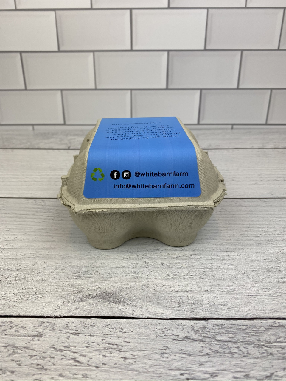 Back view of 4-Egg iMagic Custom Carton Label - Fresh Eggs in Grass attached to paper pulp carton on a counter in front of a brick wall