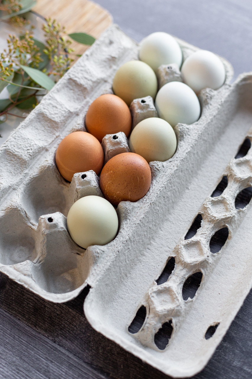 Open lifestyle image of farm fresh eggs in a closed view style egg carton surrounded by flowers