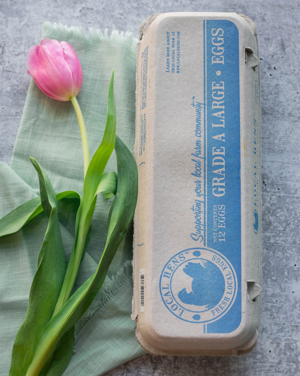 Closed blue Local Hens® Grade A Large Printed Paper-Pulp Carton with UPC on a table next to a pink flower