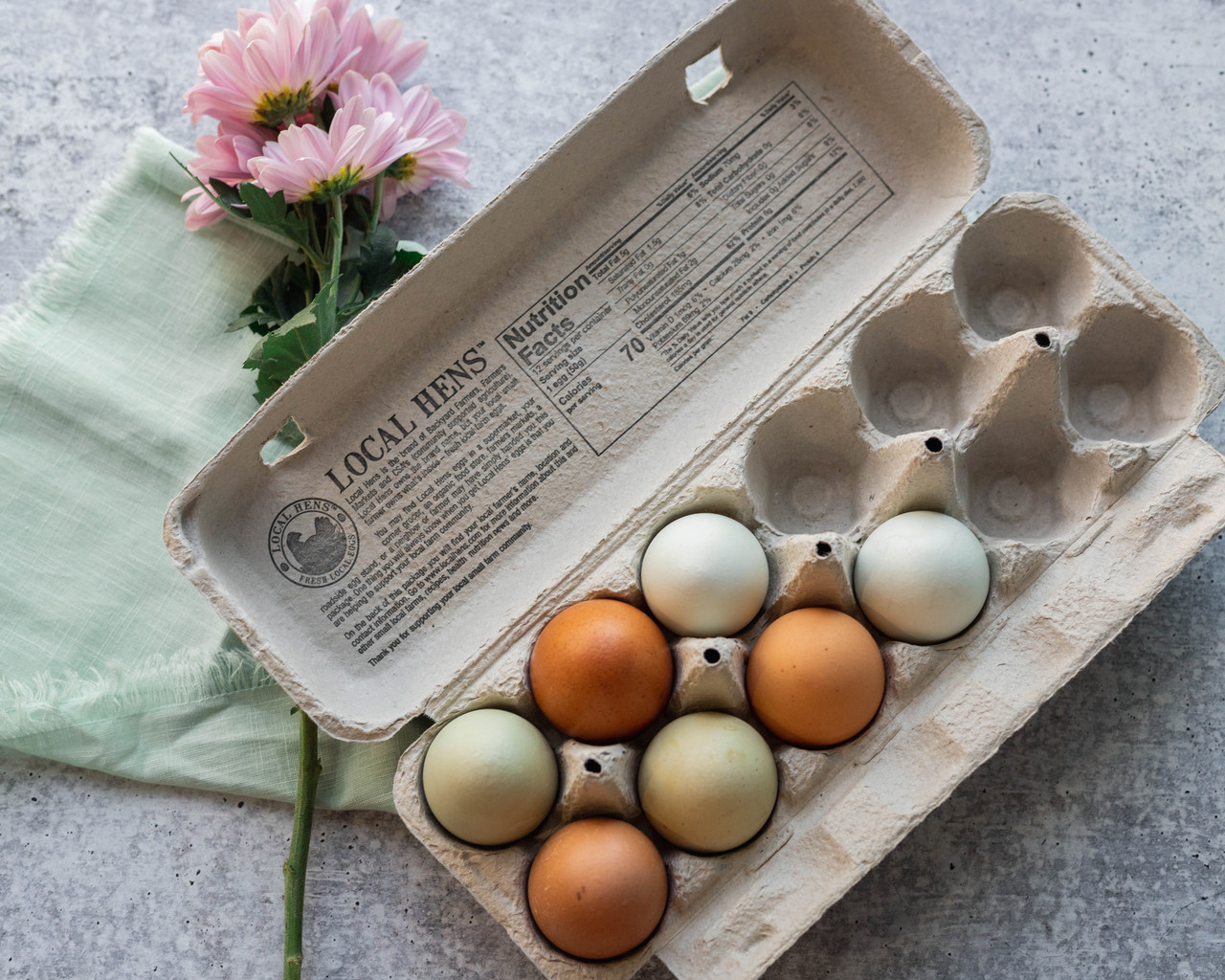 Open egg-filled blue Local Hens® Grade A Large Printed Paper-Pulp Carton with UPC on a table next to a pink flower
