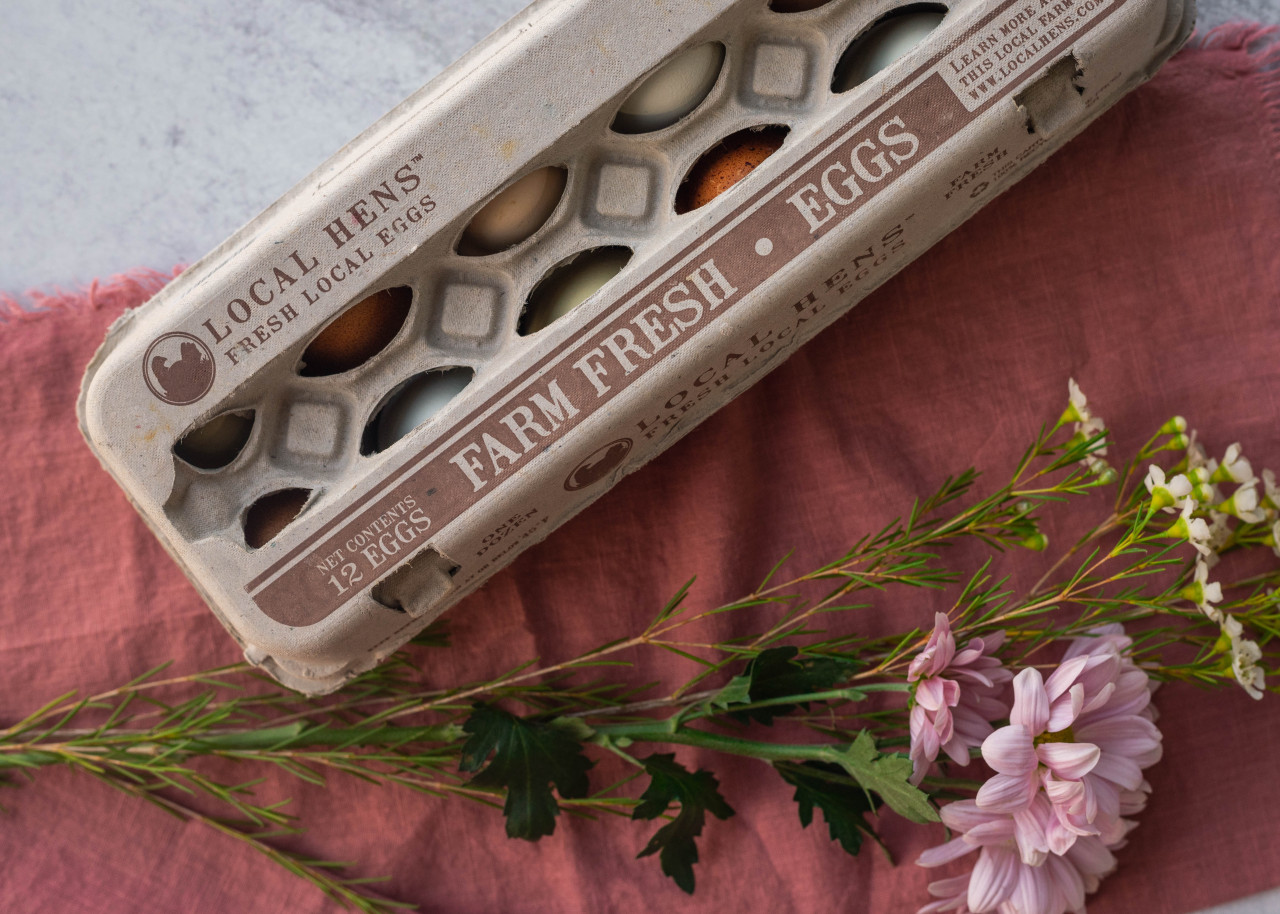 Product photo of closed Local Hens® Jumbo Cell No Grade/No Size Printed Paper-Pulp Carton with UPC surrounded by flowers