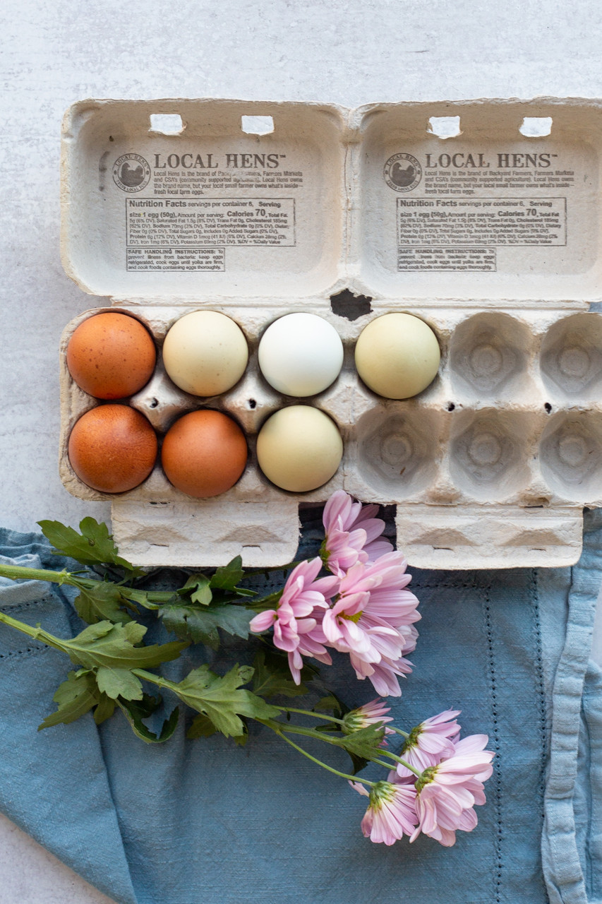 Two open Local Hens® Printed Split 6-Egg No Grade/No Size Paper-Pulp Carton with UPC next to each other surrounded by pink flowers and filled with multi-color eggs