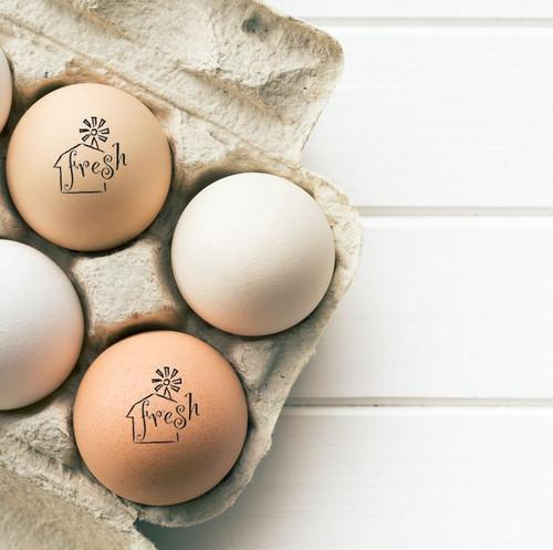 farm fresh egg stamp on brown eggs in carton