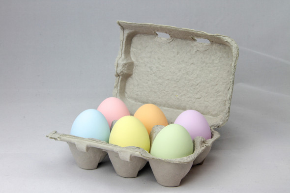 Six fake ceramic pastel multicolored nest eggs on a grey background