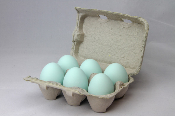 Six teal ceramic nest eggs in a brown paper pulp carton with grey background