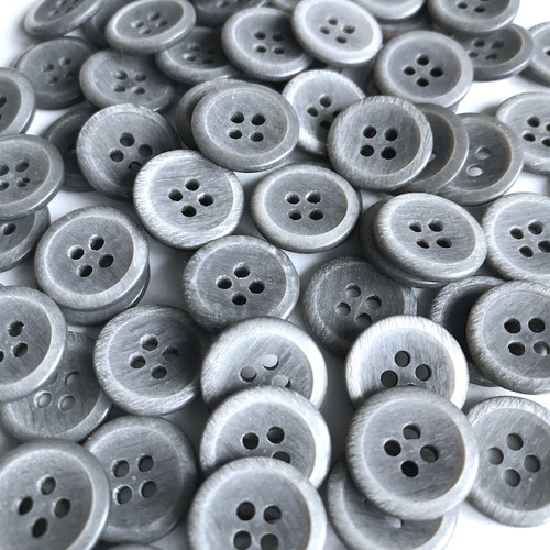 Silver grey button with matt centre and four holes.