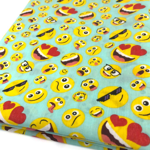 Happy emoji on aqua background printed poly cotton fabric.