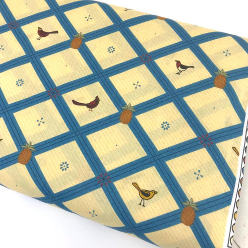 Small birds with blue lattice on cream yellow 100% cotton.