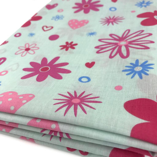 Mint polycotton with medium size flowers and hearts printed in red, pink and blue.