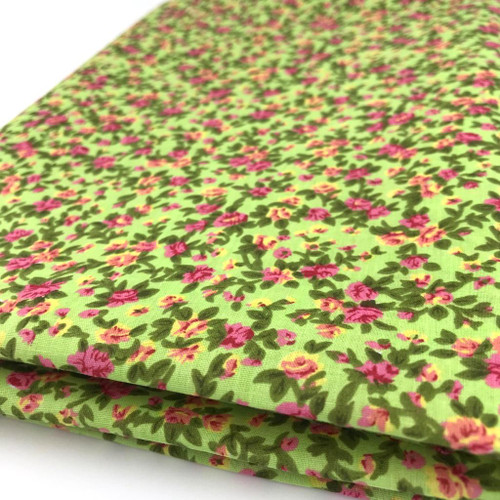 Tiny rose like flowers in pink and yellow with green foliage printed on mint polycotton.