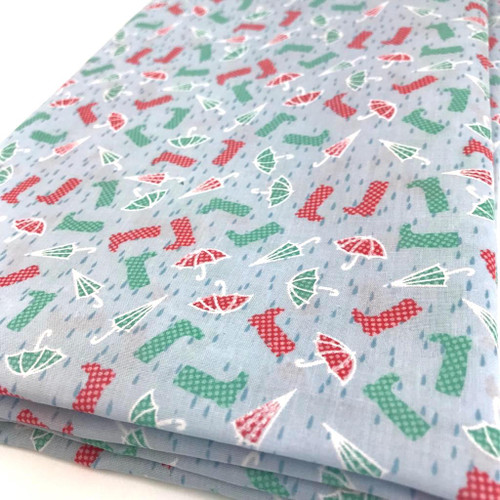 Red and green miniature wellies and brollies printed on sky blue background polycotton fabric.