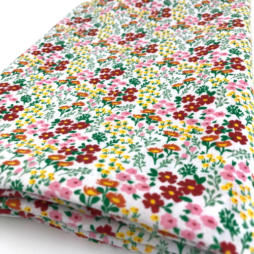 Delightful small flowers in  many summery colours printed on white polycotton fabric.
