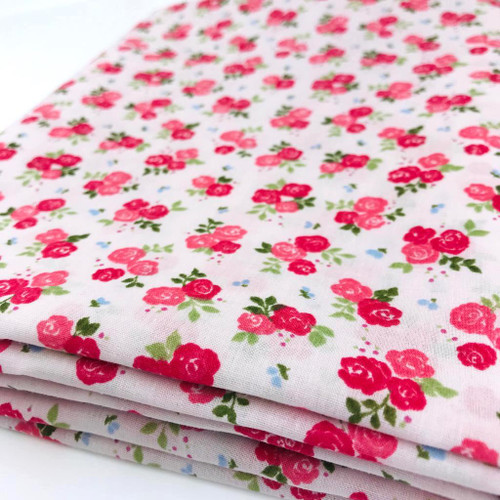 Small  hot pink rose flower on light pink polycotton fabric with green foliage and tiny blue flowers.