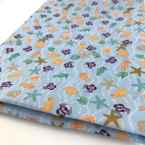 Sea shore creatures printed in orange, green, gold and purple on sky blue polycotton fabric.