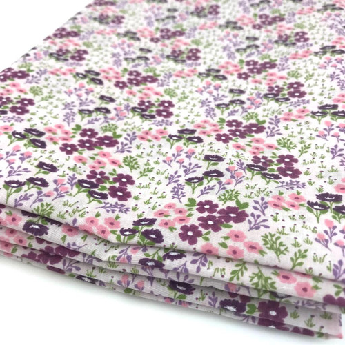 Delightful small pink and purple flowers printed on white polycotton fabric.