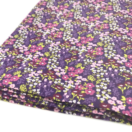 Delightful small pink and purple flowers with purple and green leaves printed on purple polycotton fabric