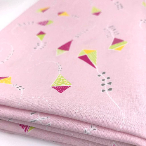 Pink cotton fabric with flying kites in yellow, pink and green. a white tail with silver grey bows.