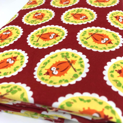 Red cotton fabric with orange owls set in a yellow circle with green vine leaves and a white scolloped border.