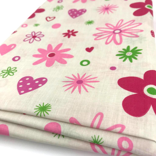 Pink and green medium flowers and hearts printed on cream polycotton fabric.