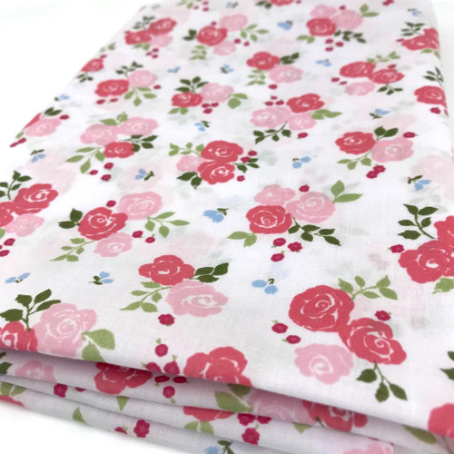 Hot and pale pink rose flower on white polycotton fabric with green foliage and tiny blue flowers.