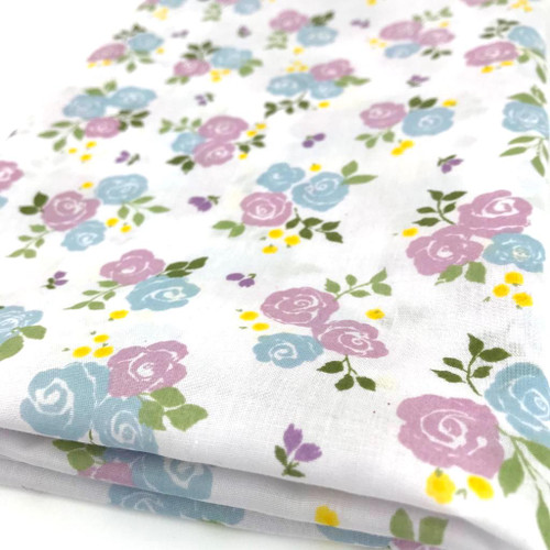 Lilac and blue rose flower on white polycotton fabric with green foliage and tiny purple flowers.
