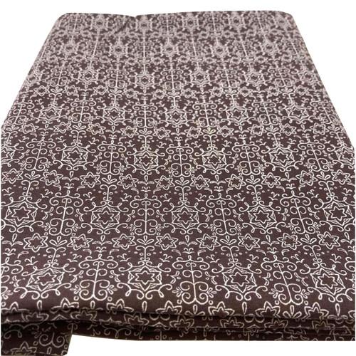 Star filigree print on brown cotton fabric.