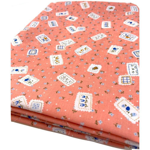 Peach polycotton fabric with ditsy flower stamp design.