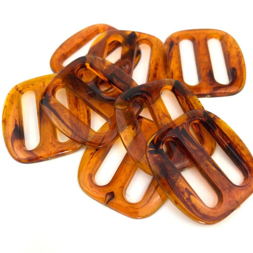 Acrylic amber buckle with slide bar.