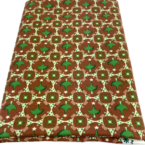 Green Christmas trees and stars printed on brown 100% cotton fabric. Medium weight fabric 56 inches wide.