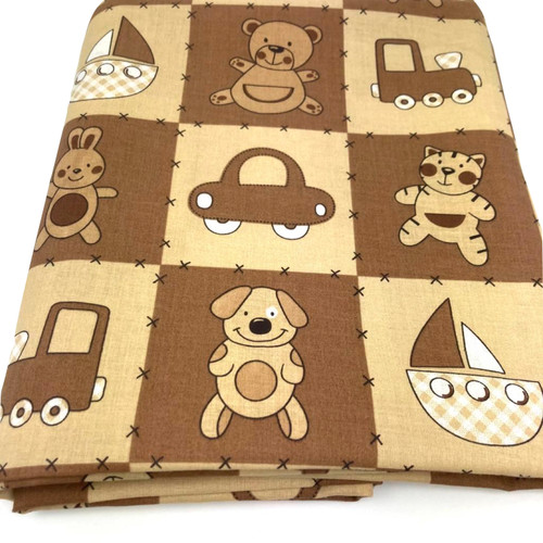 Beige and brown squares on cotton fabric each with a car, teddy, boat or truck printed in the centre.