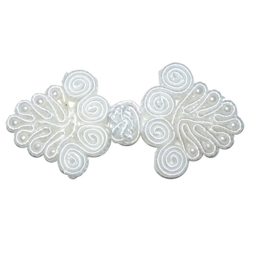 Small white frog fastener with central knot and intricate entwined scroll sides to decorate and fix in place.