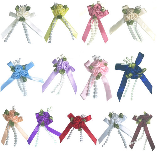 Variety of colourful small satin silk ribbon rose flowers arranged in a cluster of three for craft projects, sewing, card making and scrapbooking.