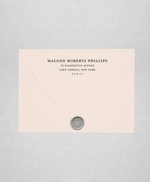 Blush wedding envelopes with black return addressing and silver wax seals