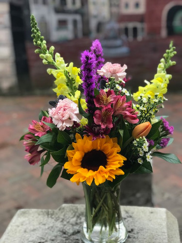 Let one of our very talented designers put together a mix of delphinium, snap, sunflower, tulips, carnations, alstro, poms, statice, aster, hydrangea and mini calla's to put a smile on someone's face.