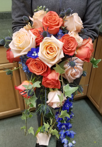 Beautiful peach and coral roses, hydrangea, thistle, delphinine and ivy