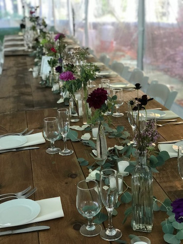 This unique style bud vase centerpieces are custom to your wedding colors. This gives a long table more dimensions with the mixed bud vases, different flowers in each or the same with some elegant greenery along the table. Starting price is $80.00 and up depending on how large of a table and vases needed
