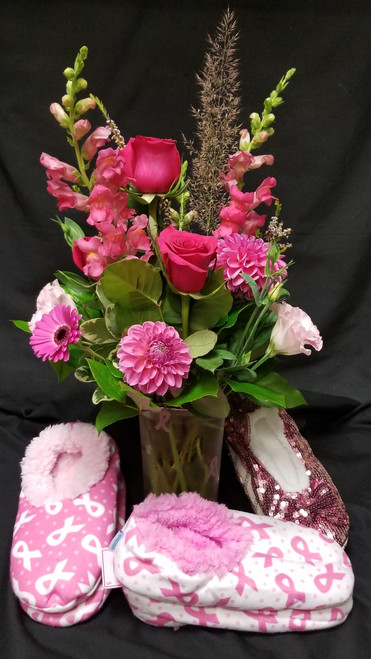 """October is Breast Care Awareness Month. We will Donate 10% of our """"pink"""" sales!  That means 10% of this floral arrangement will be donated. Stop into our Shop and check out our other items including the Snoozie Slippers shown in this photo. Thank you for all your support!"""