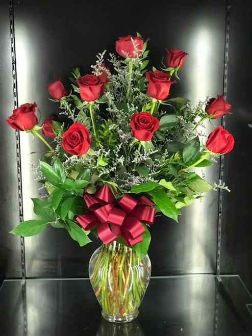 This stunning dozen Red Roses in a vase with upgraded greenery (eucalyptus & ruscus) with premium filler such as Wax Flower or Limonium