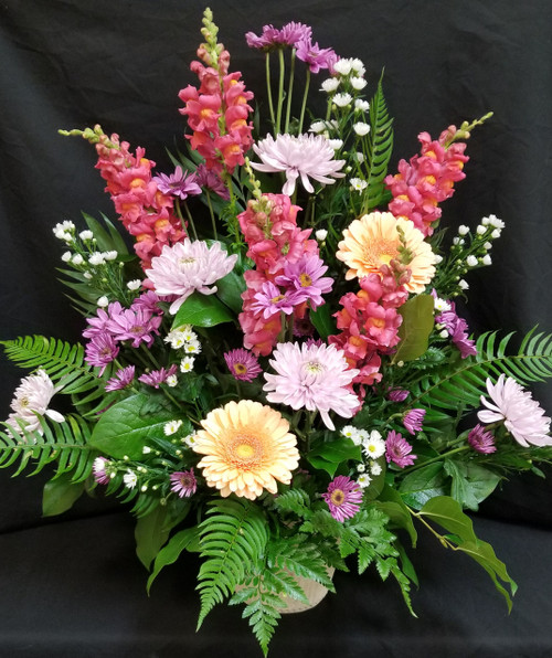 A bright and uplifting spring mix of snapdragon, gerbera daisy's, poms, cremons, Monte casino  We will use seasonal flowers and best choice on colors depending on for a Man or Woman
