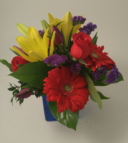 Martinique, St. Maarten, any tropical paradise is the perfect setting for this explosively colorful bouquet in a chic blue contemporary cube vase. Can't go just now? Bring the island home.  Mix of Lilies, Roses, Statice, Tulips, & Gerber daisys