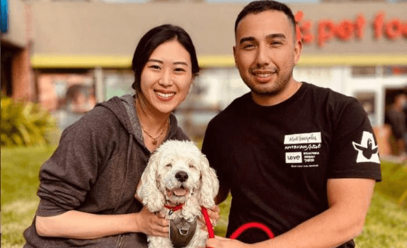 Two pet fair participants posing with a dog.