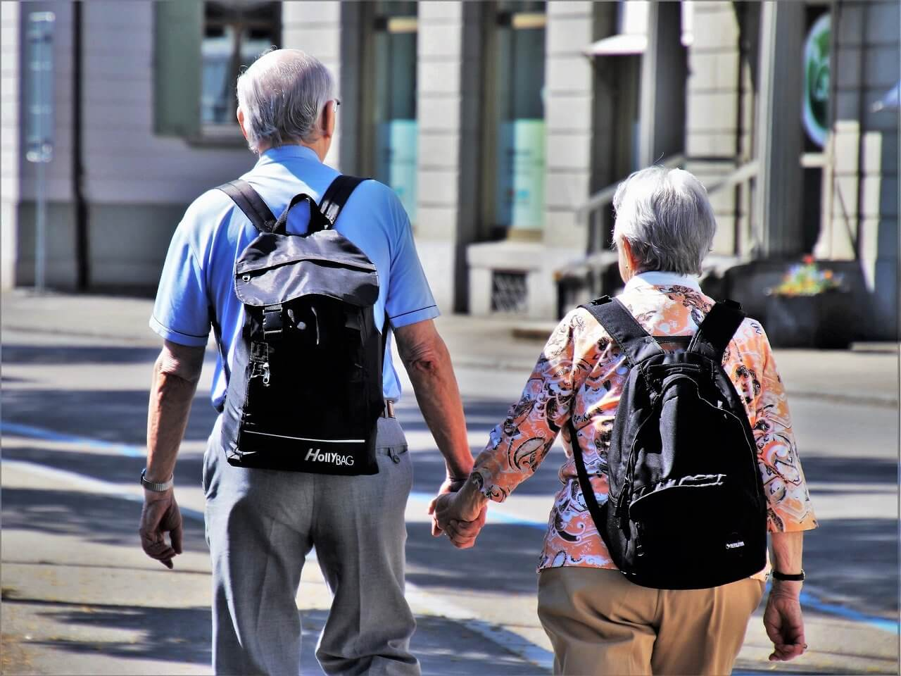 An elderly couple with backpacks holding hands and walking along an urban street in the daytime