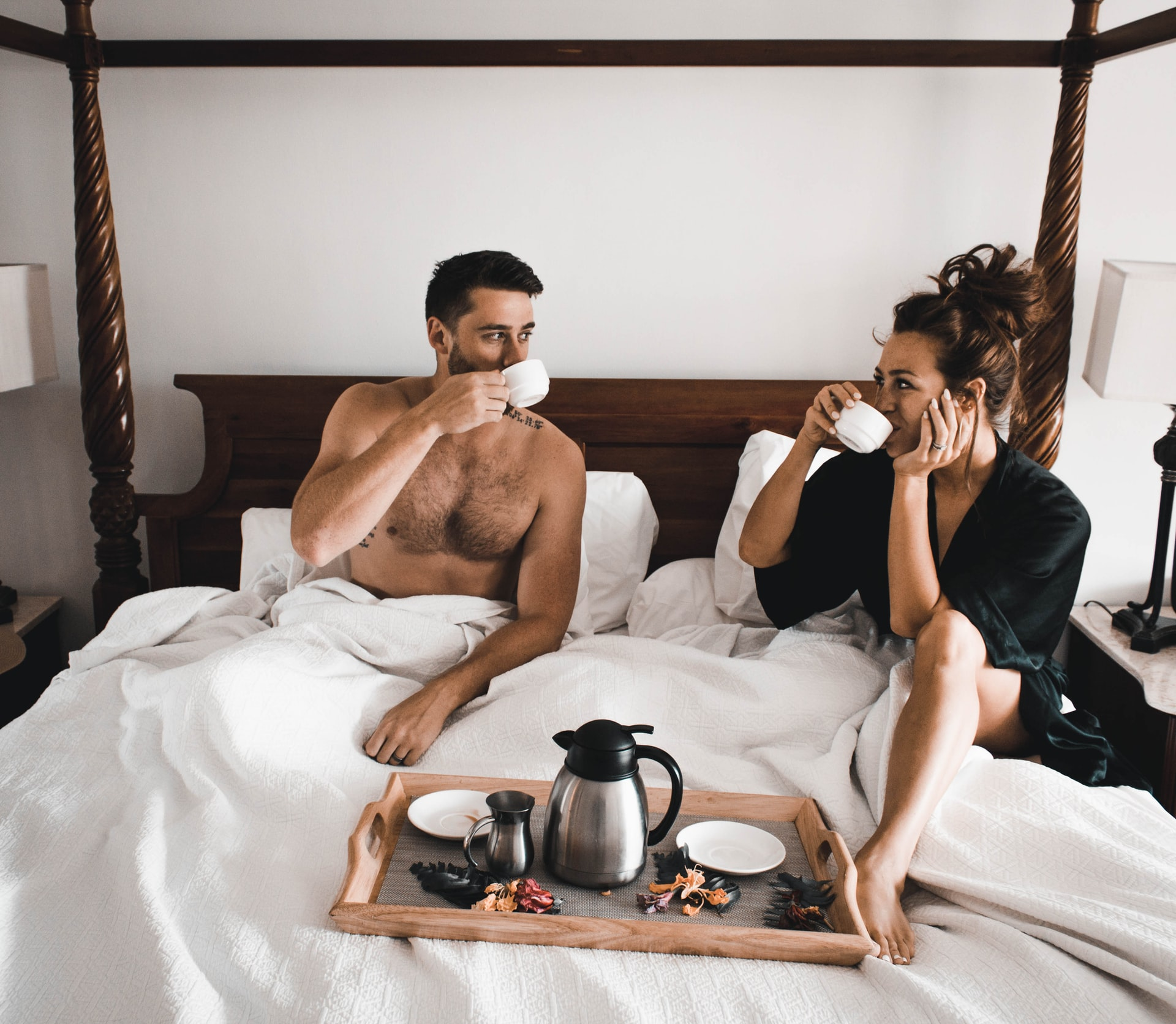A man and woman drinking coffee in bed