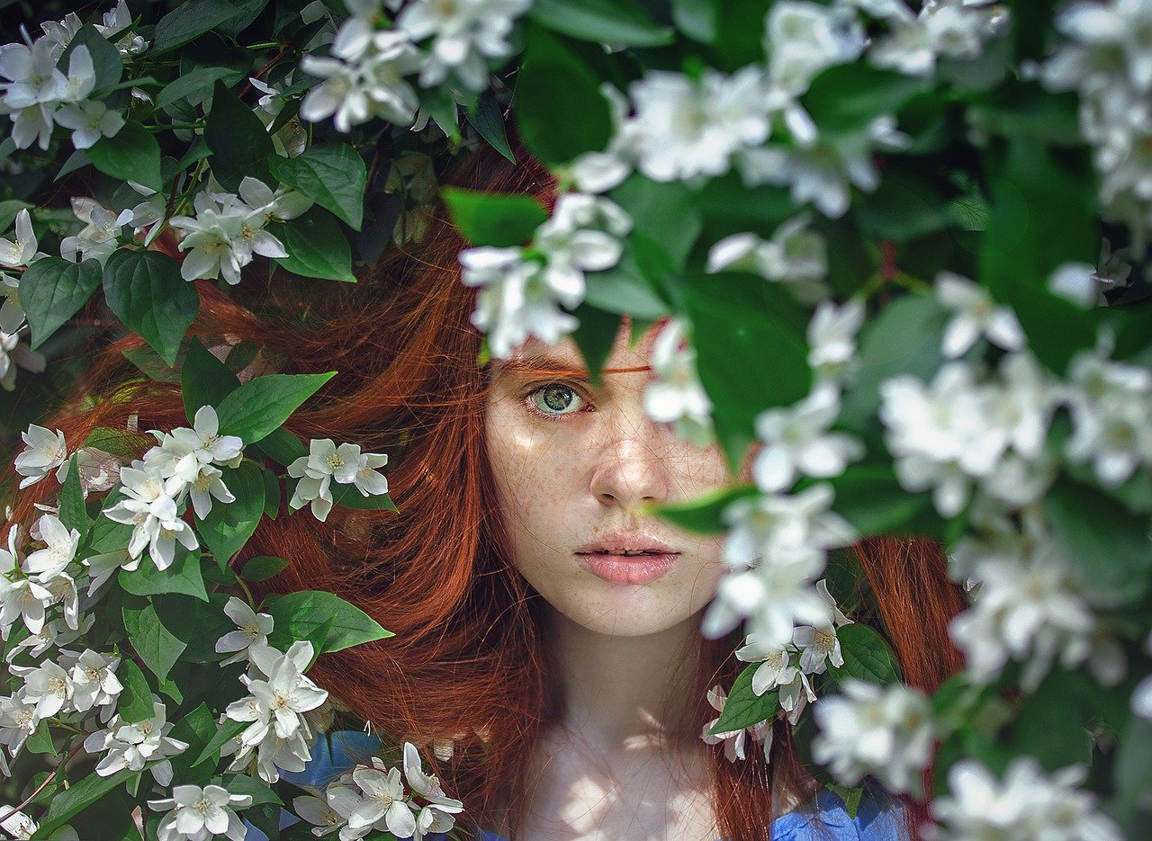 A red-haired girl hiding behind a bush covered with white flowers