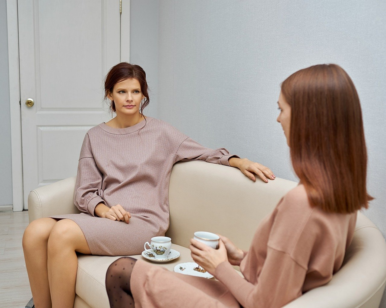Two women sitting on a couch, drinking tea and talking