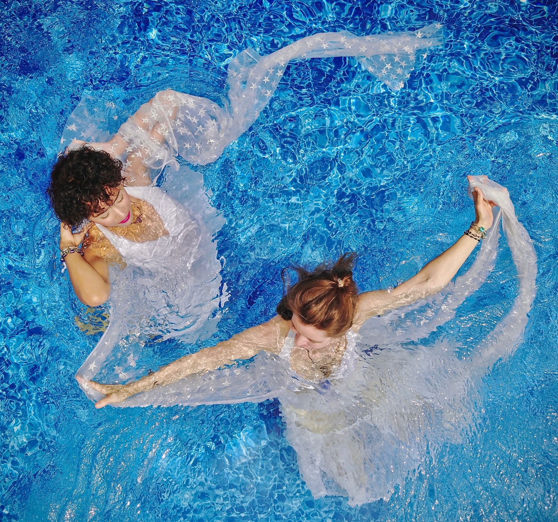 Two women exercising in a swimming pool with pink fabric