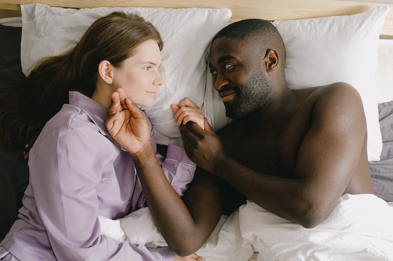 a man caressing a woman's face while lying in bed
