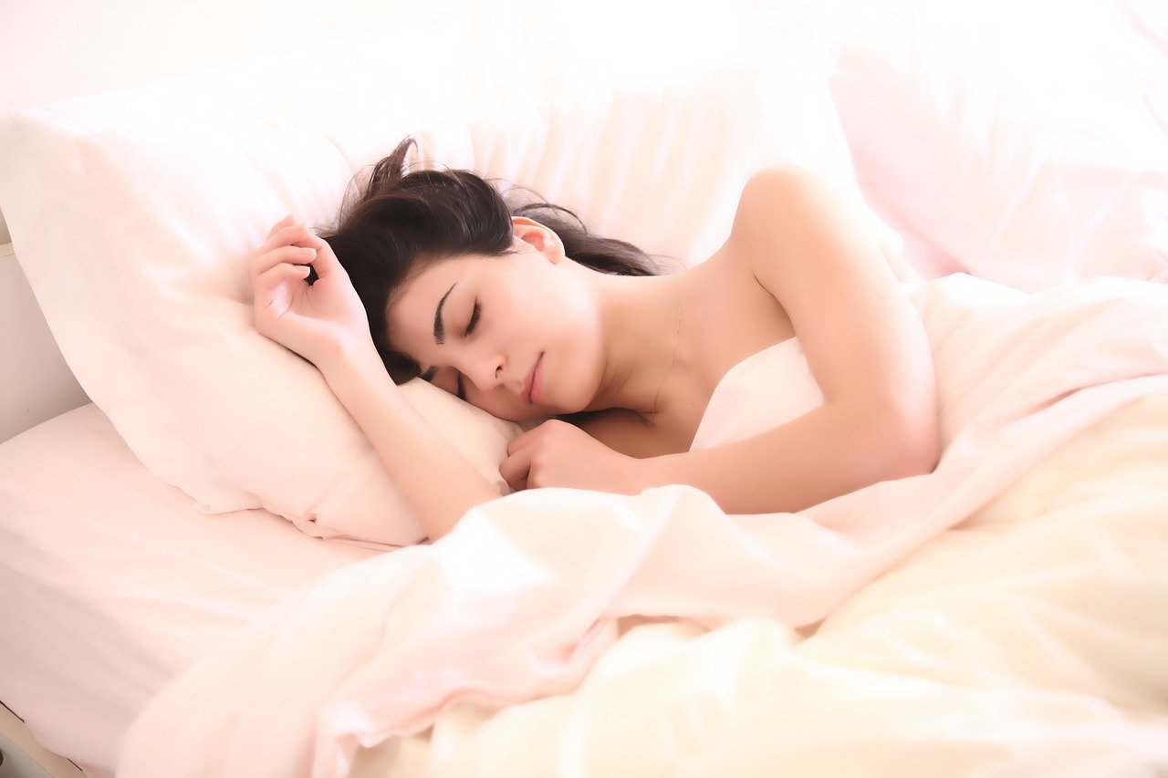 A woman sleeping in a bed with her head on a large pillow