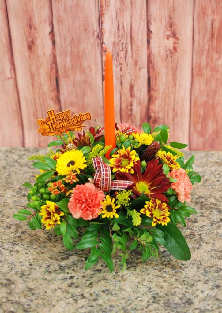 beautiful traditional candle centerpiece designed with fall flowers