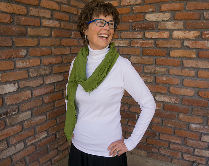 Janie in the medium turtleneck in white, paired with a bias fringe scarf